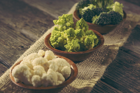 Fresh pieces of Romanesco broccoli, broccoli and cauliflower in small rustic wooden bowls. Selective focus on the Romanesco broccoli