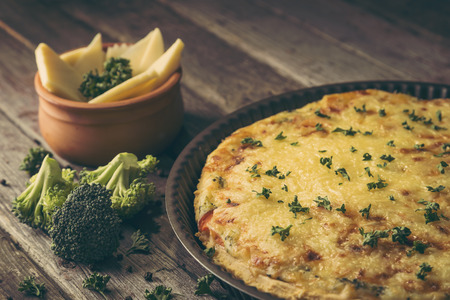 Fresh vegetable pie served in a baking tray on a rustic wooden table. Selective focus on the pie