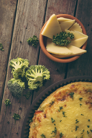 Table top shot of a fresh vegetarian pie served in a baking tray on rustic wooden table. Selective focus on the broccoli and cheese Stock Photo
