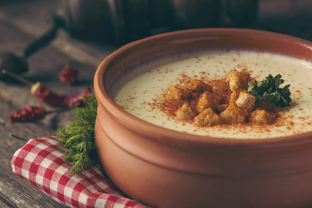 Bowl of cauliflower cream soup decorated with grounded red pepper and some croutons on a rustic wooden table. Selective focus on the croutons Stock Photo