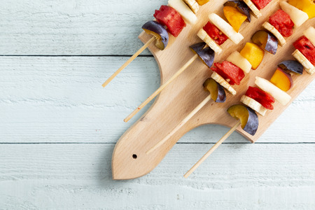 Table top shot of a colorful, healthy fruit salad portions served on barbecue sticks as a summer dessert Stock Photo