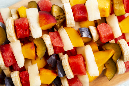 Colorful mixed fruit salad served on barbecue sticks. Selective focus