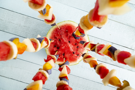 Top view of colorful mixed seasonal fruit salad served on barbecue sticks, stuck in a watermelon half as a summer party dessert. Focus on the watermelon half