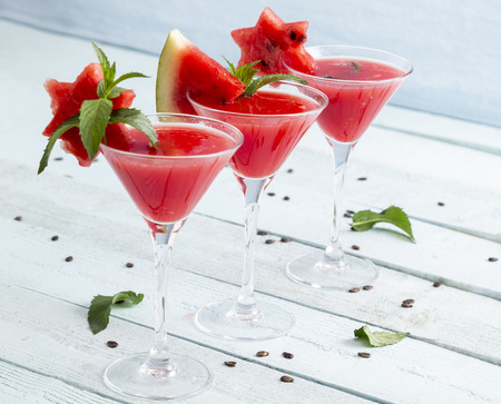 Cold watermelon cocktails served in martini glasses as a summertime refreshment. Focus on the glass in the middle