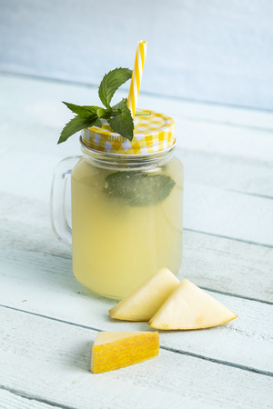 Cold melon juice served in a jar, decorated with mint leaves and melon slices. Focus on the mint leaves and the jar