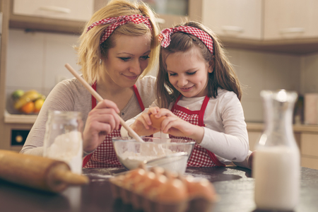 Young mother in the kitchen baking dough with her daughter, daughter adding an egg while mother is stirring the flour. Focus on the mother