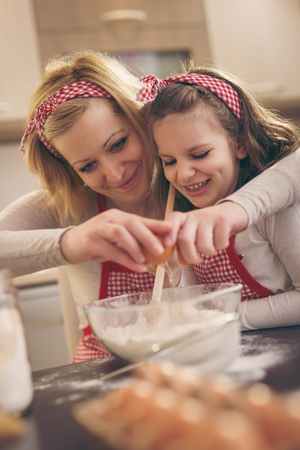 Young mother in the kitchen baking dough with her daughter, breaking an egg while daughter is stirring the flour