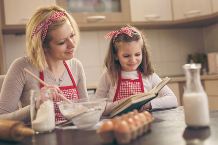 Mother and daughter making cookies in the kitchen, looking for a recipe in a cookbook. Focus on the daughter Stock Photo