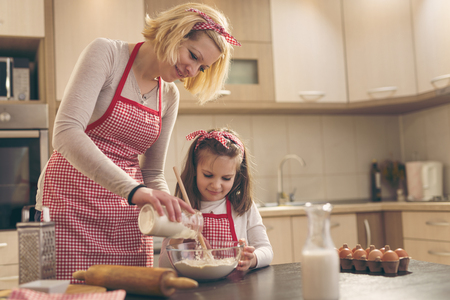 Mother and daughter baking dough in the kitchen; mother adding flour from a jar while daughter stirring with a kitchen spoon