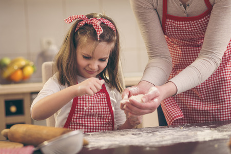 Little girl sprinkling flour over the kitchen table, helping her mother to bake a pizza dough Stock Photo