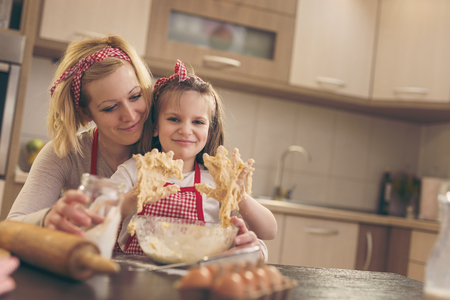 Beautiful girl kneading dough with her mother in a kitchen, having fun