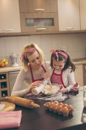 Beautiful mother and daughter having fun in the kitchen; mother pouring milk while daughter is kneading dough, stiring flour with kitchen spoon