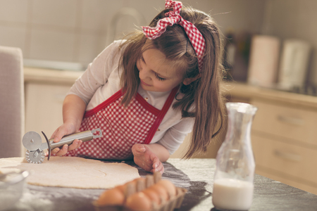 Beautiful little girl with apron in the kitchen cutting dough for rolls with pizza cutter Stock Photo