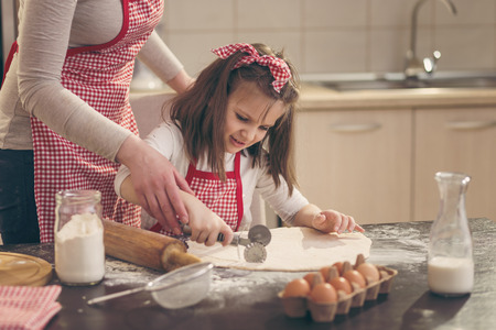 Beautiful little girl with apron in the kitchen cutting dough for rolls with pizza cutter with the assistance of her mother
