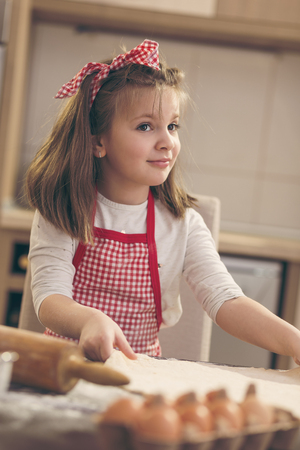 Little girl having fun in the kitchen while helping her mother to make a pizza dough