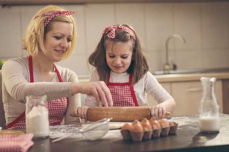 Mother and daughter baking cookies in the kitchen; little girl using a rolling pin, kneading cookie dough