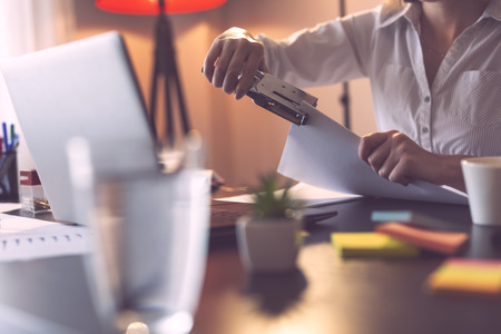 Detail of businesswoman holding a stapler and joining pages of a contract with it. Focus on the stapler Stock Photo