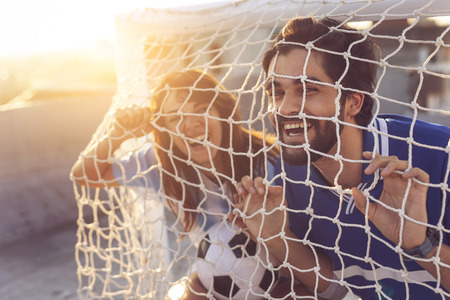 Couple in love wearing football jerseys on a building rooftop after a match, peeking through a goal net and having fun