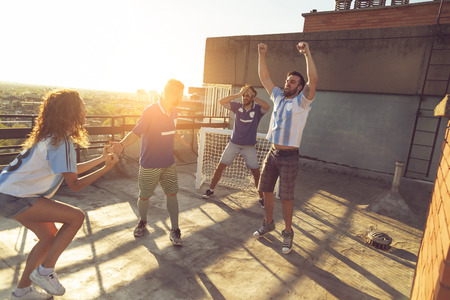 Group of young friends having fun playing football on a building rooftop. One team scored a goal celebrating while the other one anxious because of losing the game Stock Photo