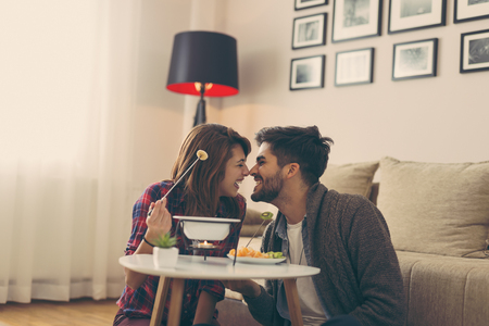 Couple in love dipping fruit into melted chocolate, relaxing and enjoying romantic moments together Stock Photo