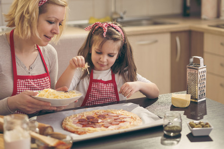 Mother and daughter in the kitchen making pizza, putting the cheese on the pizza dough. Focus on the daughter 免版税图像