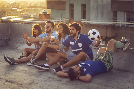 Group of young friends watching a football match on a building rooftop, cheering and drinking beer. Banque d'images