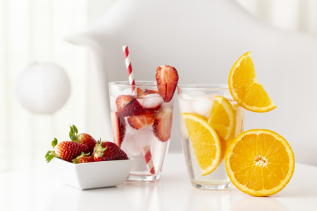 Glasses of infused water with fresh orange slices and strawberries. Focus on the glass with oranges Stockfoto