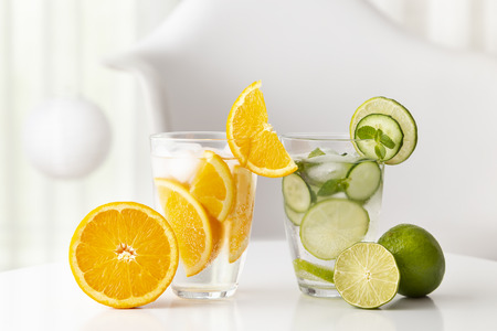 Glasses of infused water with fresh lime, cucumber and mint leaves and orange slices