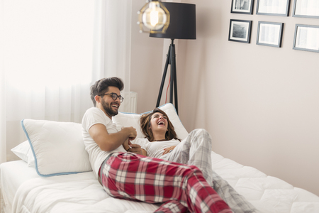 Young couple in love lying in bed, cuddling and laughing after waking up. Focus on the girl Stock fotó
