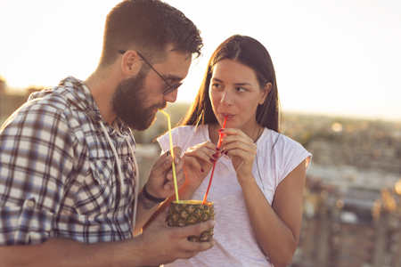 Young couple in love drinking a pineapple cocktail and having fun at rooftop party in sunset