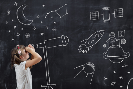 Schoolgirl standing in front of a blackboard, watching stars through a chalk-drawn telescope, learning about space and astronomy Foto de archivo