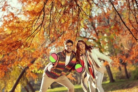 Couple in love having fun on an autumn day in the park, playing toss and catch the ball game