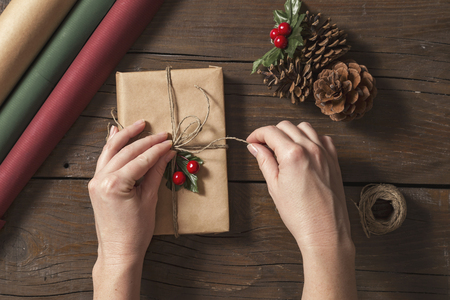 Top view of female hands wrapping Christmas presents on wooden table background Stock Photo