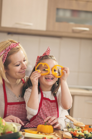 Beautiful mother and daughter having fun making salad in the kitchen, holding pepper slices as glasses and peeking. Focus on the daughter