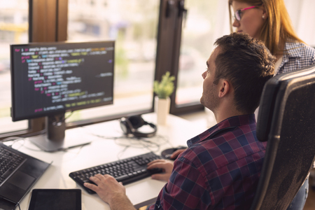 Two senior developers working in a software developing company office. Focus on the man sittig
