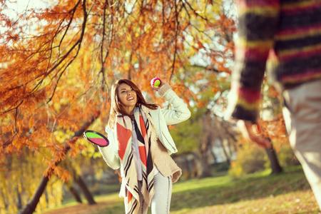 Verliebte Paare, die sich an einem Herbsttag im Park amüsieren, werfen und das Ballspiel fangen Standard-Bild