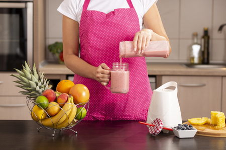 Detail of female hands pouring a freshly made raspberry smoothie in a jar; woman wearing apron standing in the kitchen, making smoothie for breakfast