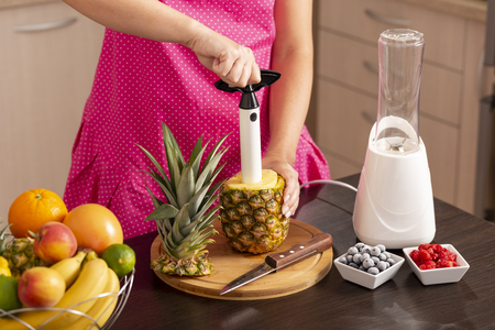 Woman peeling a pineapple with a pineapple cutter, making a fresh, healthy, raw fruit smoothie 스톡 콘텐츠