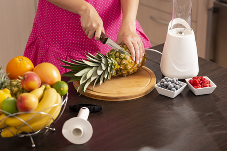 High angle view of a woman cutting a pineapple top with a kitchen knife on a cutting board in order to peel it with a pineapple cutter 스톡 콘텐츠