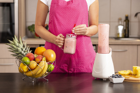 Detail of female hands holding a freshly made raspberry smoothie in a jar; woman wearing apron standing in the kitchen, making smoothie for breakfast
