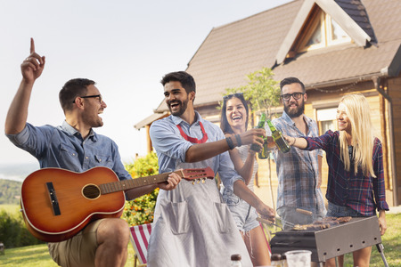 Group of friends having a barbecue party outdoors, drinking beer, grilling meat, playing the guitar and having fun