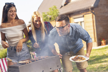 Group of friends making barbecue in the backyard and having fun on a sunny summer day. Focus on the man