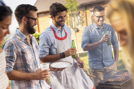 Group of friends making barbecue in the backyard, drinking beer and having fun on a sunny summer day. Focus on the man in the middle 스톡 콘텐츠