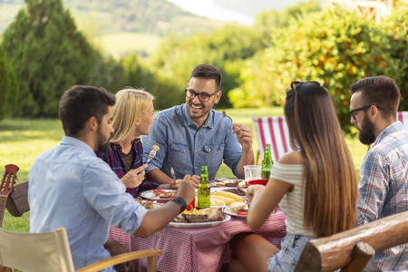 Group of friends having an outdoor barbecue lunch, eating grilled meat, drinking beer and having fun. Focus on the man in the middle