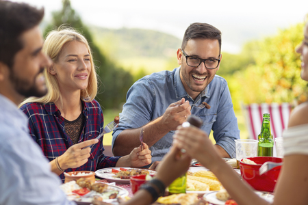 Group of friends having an outdoor barbecue lunch, eating grilled meat, drinking beer and having fun. Focus on the man on the right