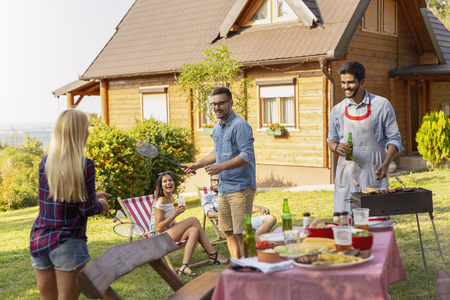 Group of friends having a backyard barbecue party, grilling meat, drinking beer, playing badminton and having fun on a sunny summer day. Focus on the man playing badminton