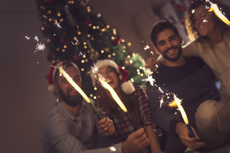 Group of young friends having fun at a New Years celebration, holding sparklers at a midnight countdown. Selective focus on the sparklers
