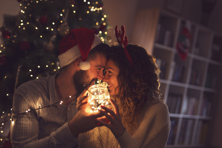 Beautiful couple in love sitting on the living room floor next to a Christmas tree, holding a jar with Christmas lights 스톡 콘텐츠