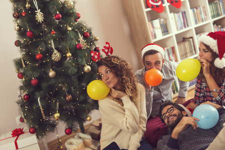 Group of young friends siting on the floor next to a Christmas tree, wearing Santas hats, blowing balloons and having fun. Focus on the girl on the left 스톡 콘텐츠