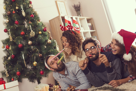 Group of young frineds lying on the floor next to a Christmas tree, having fun blowing party whistles. Focus on the couple on the left